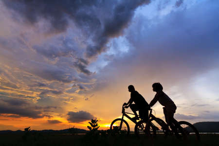 Beautiful Couple on bicycles on the brink of a rock and look afar from rock breakage