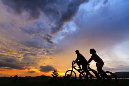 Schönes Paar auf Fahrrädern am Rande eines Rock und Aussehen der Ferne aus Rock Bruch