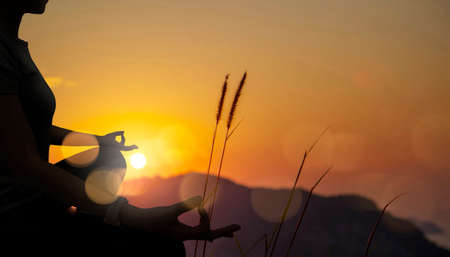 The silhouette of woman sitting yoga alone,Relax and meditate,mental health concept with nature spiritual.