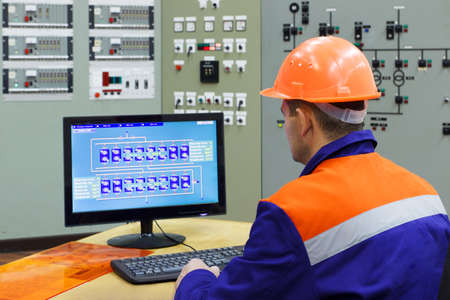 experienced operator: Engineer at the computer on main control panel of gas compressor station, focus on back Stock Photo