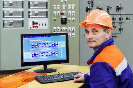 skilled operator: Engineer at the computer on main control panel of gas compressor station, focus on face