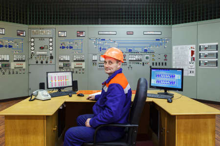 experienced operator: Engineer sitting at the table on main control panel of gas compressor station