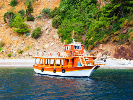 desolated: Orange yacht for tourists staying in deserted bay, Turkey Editorial