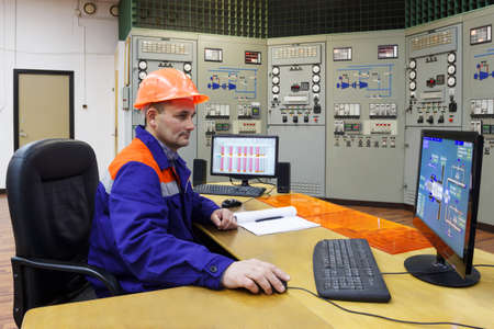 experienced operator: Engineer watching parametrs turbines on the monitor in main control panel of gas compressor station