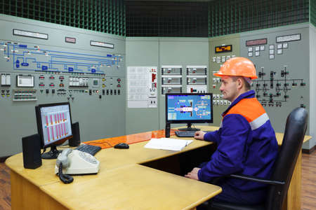 experienced operator: Engineer at the workplace on main control panel of gas compressor station Stock Photo