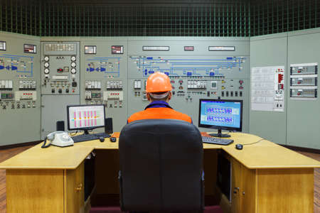 setup operator: Engineer sitting at the workplace on main control panel of gas compressor station
