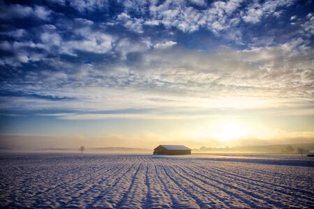 in conjunction: Hut at sunrise, winter with snow and light haze in conjunction with a dark blue sky, in this there are beautiful cumulus clouds