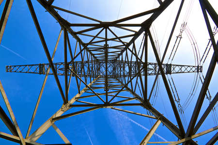 struts: In the center of power poles photographed against a deep blue sky