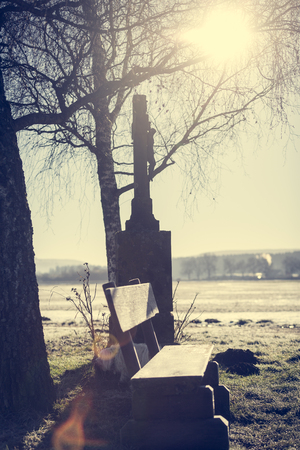 sun lit: Resting place at a crossroads of the sun lit up on a cold winter morning. Stock Photo