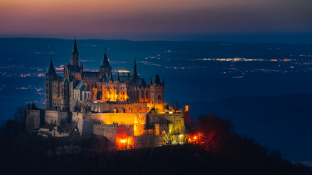 The Hohenzollern Castle, the ancestral seat of the House of Hohenzollern, photographed the illuminated villages in the background in the evening.