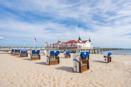 The historic pier of Ahlbeck on the sunny island of Usedom on the Baltic Sea. In the foreground empty beach chairs. Redakční