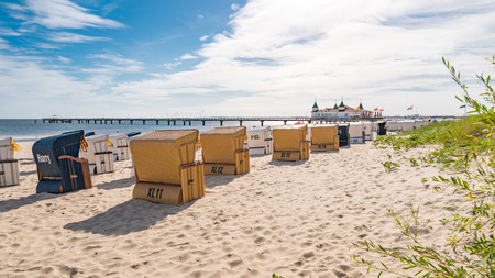 A sandy beach with beach chairs in the sunshine and in the background the historic pier of Ahlbeck