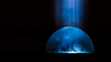 Frozen soap bubble in freezing winter weather on a light source.