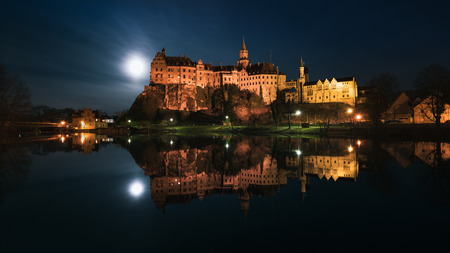 The Hohenzollern Castle in Sigmaringen is located directly on the Danube, the full moon next to the castle illuminates the surroundings.