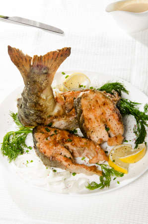 pink salmon: grilled steaks of pink salmon on a round white plate with Lemon and dill on a white background with spices and sauce