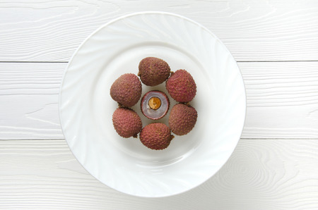 litschi: several lychees on a white circular plate on a white wooden background, top view Stock Photo