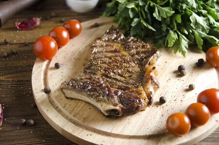 pounder: grilled steak on a wooden board on a wooden background with parsley salt pepper and tomatoes