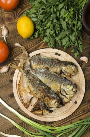 sunfish: fried fish on a wooden board on a wooden background with spices