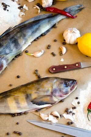 grinling fish with vegetables onions garlic lemon on baking paper Stock Photo