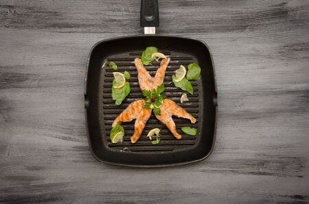 pink salmon: pink salmon steaks grill pan on gray wooden background