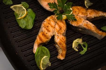 pink salmon: group of pink salmon steaks grill pan on gray wooden background