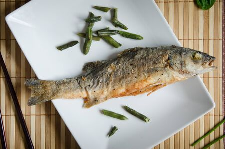 baked sea bass rectangular white plate on a wooden background