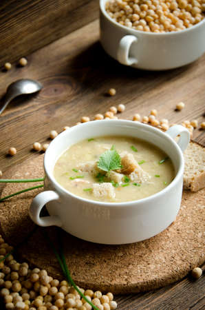 white plate pea soup on a brown wooden background