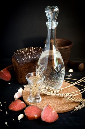 Wodka Glas Dekanter Weizen Lachs auf schwarzem Hintergrund stilleben