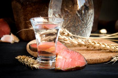 pounder: vodka glass decanter wheat salmon garlic on black background close up Stock Photo