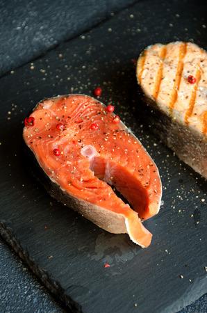 Salmon steaks pepper salt black plate on dark background close-up Stock Photo