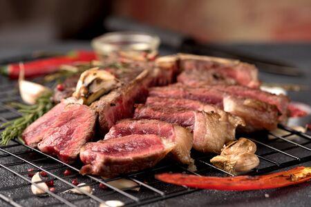rare steak Porterhouse pepper rosemary garlic on a dark background close up