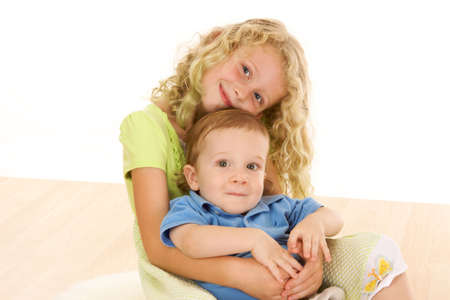 Young school age girl embraces younger brother in studio portrait Stock Photo - 5445334