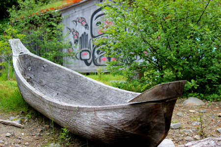 Native american dugout canoe on land is displayed in front of a native building