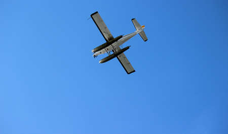 cloudless: A float plane flies high overhead  Photo is shot on cloudless blue sky  The pontoons are clearly visible   Float plane flying in blue sky