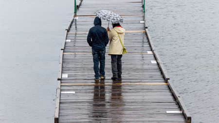 A couple a standing beside each other on a wet pier  It is raining and one person holds an umbrella  The water on the right side of the pier is rippling and the water on the left is smooth  Stock fotó