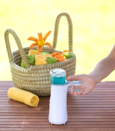 tidiness: liquid soap and towels rolled in basket on wooden board