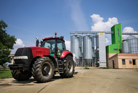 mechanization: tractor parked in front of grain silos Stock Photo