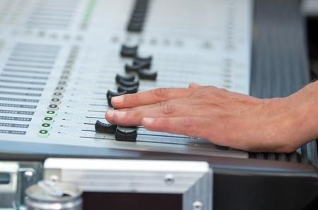 soundboard: Man hand works on soundboard at concert