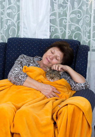 Old woman and her cat sitting in armchair covered with blanket photo