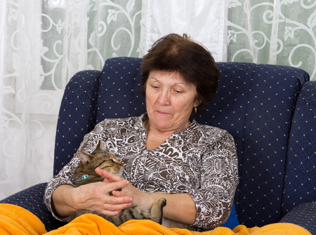 Conceived woman cuddles her cat in bosom photo