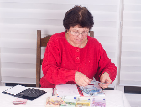 Woman counting money on table with calculator and notebook photo