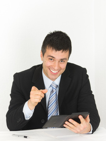 Smiling young businessman with calculator pointing finger at camera photo