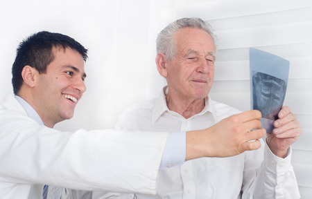 Young doctor smiling and showing a x-ray to senior patient photo