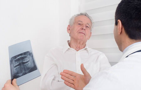 Young doctor showing and explaining a x-ray to senior patient photo