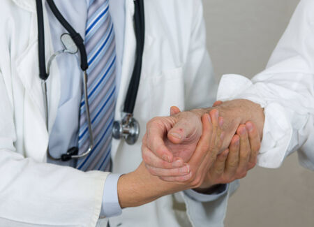 osteo: Doctor in white coat holding senior mans hand