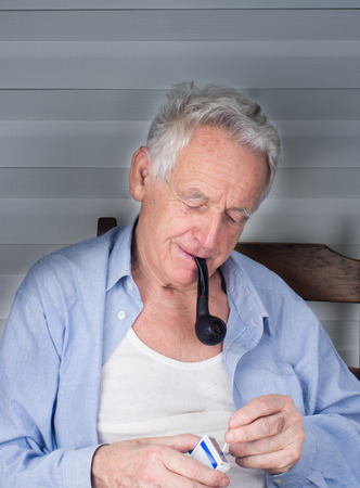 Old man lighting up smoking pipe with matches photo
