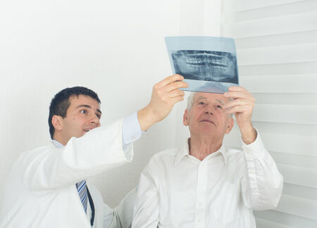 Young doctor showing a x-ray to senior patient photo