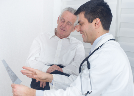 Young doctor showing and explaining x-ray to senior patient photo