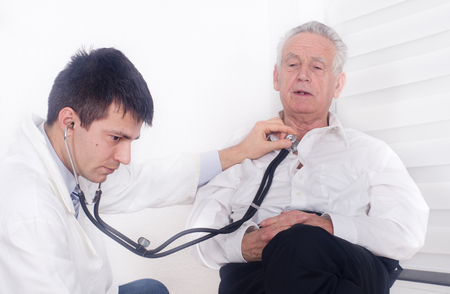Young doctor listening heartbeat with stethoscope of old man photo