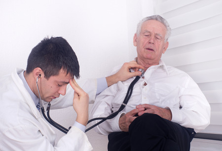 listening to heartbeat: Young doctor listening heartbeat with stethoscope of old man Stock Photo